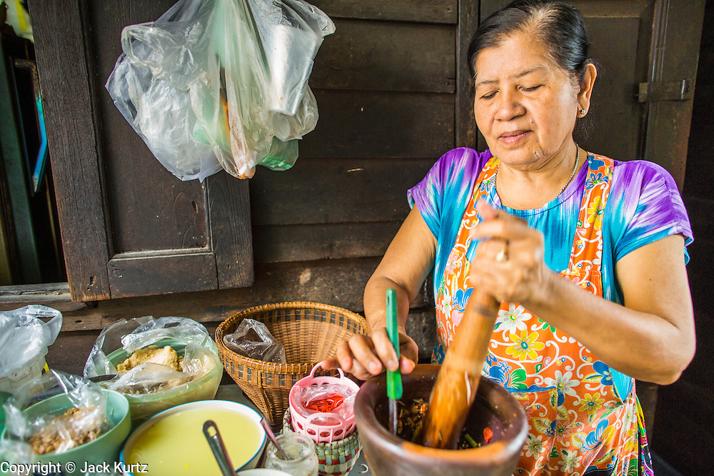 """10 JANUARY 2013 - BANGKOK, THAILAND:  A Buddhist woman prepares Thai Papaya Salad, called """"Som Tom"""" at a lunch counter in front of her home in the Baan Krua neighborhood in Bangkok. The Ban Krua neighborhood of Bangkok is the oldest Muslim community in Bangkok. Ban Krua was originally settled by Cham Muslims from Cambodia and Vietnam who fought on the side of the Thai King Rama I. They were given a royal grant of land east of what was then the Thai capitol at the end of the 18th century in return for their military service. The Cham Muslims were originally weavers and what is known as """"Thai Silk"""" was developed by the people in Ban Krua. Several families in the neighborhood still weave in their homes.   PHOTO BY JACK KURTZ"""