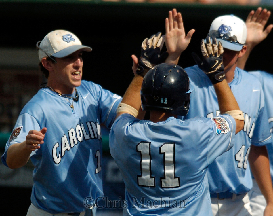 06/20/2006 North Carolina's Mike Cavasinni is greeted at home plate after scoring  during game eleven of the College World Series in Omaha Nebraska Wednesday afternoon..(photo by Chris Machian/Prairie Pixel Group)