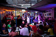 Rumba gig at a bar in Havana old town, while the crowd watches, low colourful lighting.