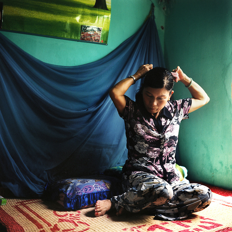 """""""I was born in 1949, in Phú Vang, 12 kilometers from Hue.  I'm from the countryside originally.  My mother gave birth to 13 children, but two died, so we had 11 - seven boys, and four girls.  I was the oldest.<br /> <br /> """"In 1967 I joined the youth volunteers.  We transported food to soldiers in the south.  In 1968, we followed the troops to Hue.  That year, we had a big fight in Hue, and I worked with the medical team.  Later I served at Xã Nam station to take care of the wounded soldiers.<br /> <br /> """"You know, I've been through many situations in which I was almost killed.  One time, when we were working at the fields, a number of B-52 jets came.  I lay down next to the stream while the B-52s destroyed the whole area.  I was lucky I survived.  When you hear the B-52s, it's just so fast - you hear the sound, and already it's making huge holes in the ground everywhere.  But after you hear that, it's already gone.  It's very hard to react; you just can't do anything about it.<br /> <br /> """"Where did we get our strength to keep fighting?  We had no choice, we had to work hard in order to liberate our country so we can reunite with our family and come back to the Fatherland.  I had a very strong connection with my other unit members.  Everyone was away from their family, away from their home, so of course we had to rely on each other, to support each other.""""<br /> <br /> Võ Thi Yên, born in 1949, photographed in her living room in Hue, Vietnam.  July 2010."""