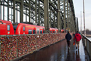 People crossing the Hohenzollern Bridge, with padlocks on representing lovers devotion, as a train goes past. Cologne, Germany.