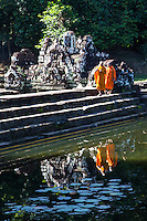 """Cambodian Monks at Neak Pean - Neak Pean """"The entwined serpents"""" is built on an artificial island with a Buddhist temple on a circular island and was constructed during the reign of King Jayavarman VII.  The temple and lake represent Anavatapta - a mythical lake in the Himalayas - with waters that are believe to cure illnesses. Neak Pean was set up for medical purposes.  The ancients believed that going into the pools would cure diseases based on the ancient Hindu belief of balance. Four connected pools represent Water, Earth, Fire and Wind. The stone statues in pavilions are meant to represent the heads of the Four Great Animals."""