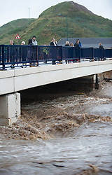 © Licensed to London News Pictures. 06/09/2013<br /> <br /> Saltburn, Cleveland, England<br /> <br /> People stand on a bridge near Cat Nab car park as heavy flooding hits in Saltburn in Cleveland.<br /> <br /> Photo credit : Ian Forsyth/LNP