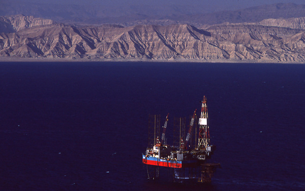 Stock photo of an offshore jack-up drilling rig in the Gulf of Suez,Egypt with the Sinai penisula background.