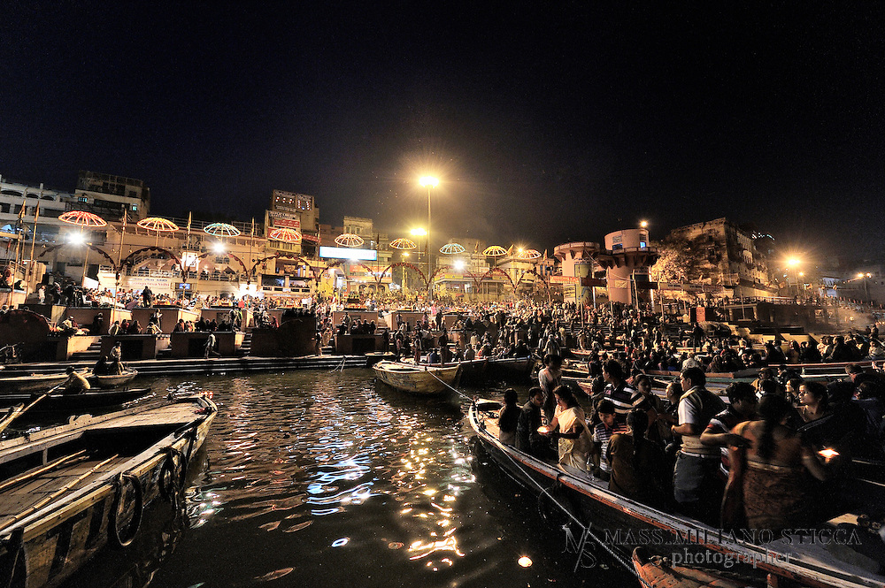 The Varanasi Ganga Aarti takes place every sunset at the holy Dasaswamedh Ghat, near Kashi Vishwanath Temple. It differs from the aartis at Haridwar and Rishikesh in that it's a highly choreographed ceremony. Although a spectacular must-see, some people consider it to be too much of an artificial and showy extravaganza to have a lot of meaning in a spiritual context.rnThe aarti is performed on a stage by a group of young pandits, all draped in saffron colored robes, with their puja plates spread out before them. It commences with the blowing of a conch shell, and continues with the waving of incense sticks in elaborate patterns and circling of large flaming lamps that create a bright hue against the darkened sky. The movement of the lamps, held in the pandits' hands, is tightly synchronized to the rhythmic chants of hymns and clang of cymbals. The heady scent of sandalwood thickly permeates the air.