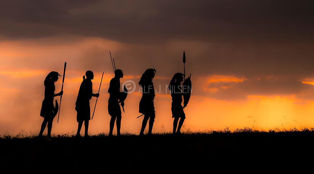 Maasai warriers against the setting sun.  Maasai Mara, Kenya.