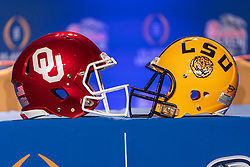 Oklahoma Sooners and LSU Tigers helmets sit on a table prior to a news conference for each team on Tuesday, Dec. 24, in Atlanta. LSU will face Oklahoma in the 2019 College Football Playoff Semifinal at the Chick-fil-A Peach Bowl. (Paul Abell via Abell Images for the Chick-fil-A Peach Bowl)