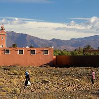 Africa, Morocco, Skoura. Women passing Mosque in Skoura.