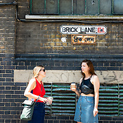 Two women standing under Brick Lane street sign