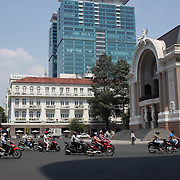 Scooters pass The Municipal Theatre, The Saigon Opera House, (right) and The Hotel Continental Saigon. Ho Chi Minh City, Vietnam. 3rd March 2012. Photo Tim Clayton