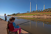 Israel, Hadera, The Hadera River the power plant's flues in the background. Children fishing in the river. Model Release available
