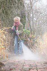 Carol Klein washing brick paths with a jet spray