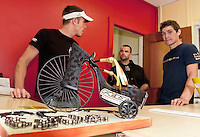 """Miles Chase, CJ Best and Samuel Tyler Evans Brown of MC Cycle admire the """"high wheeled"""" shoe created by Sue and Randy Bullerwell of All My Life Jewelers during the Downtown Still Has Sole event ongoing through Thursday.  (Karen Bobotas/for the Laconia Daily Sun)Laconia's Downtown Still Has Sole event with shoes on display at local businesses  June 24, 2011."""