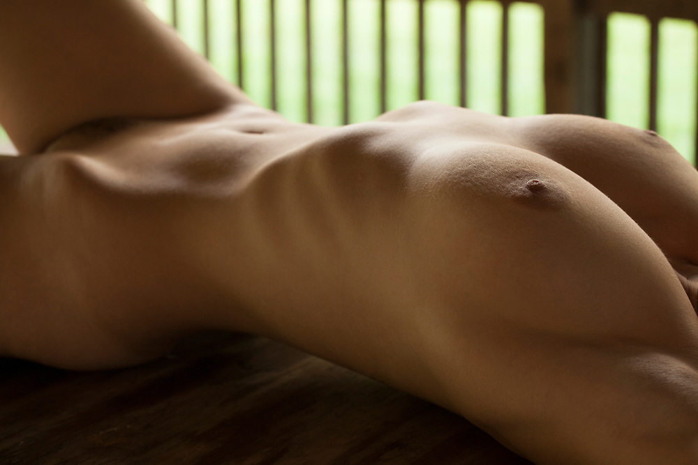 Nude woman's shapely torso reclining on porch with natural light. Porch railing in background