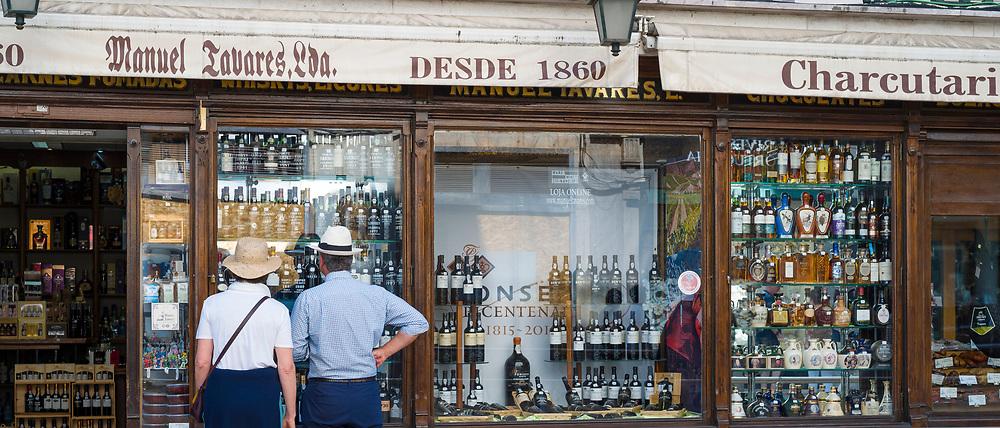 Tourists looking in window of famous Manual Tavores shop in Rua de Betesga, Praca de Figueira in Lisbon, Portugal
