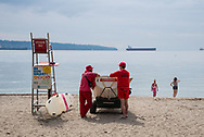 A pair of lifeguards watch the beach on a hazy summer afternoon in Vancouver, Canada