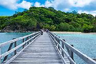 Yasawa-I-Rara, Fiji--March 8, 2018. Tourists are walking down a long wooden dock toward lush foliage on thier way to a beach in the Fiji Islands. Editorial Use Only.