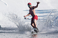 A shirtless snowboarder crosses the water during the Wacky Water Event at the Spring  Rally at Mount Peter Ski and Ride in Warwick, New York. The Spring Rally traditionally closes the season at the ski area.