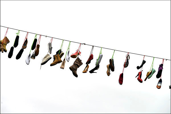 Nederland, the netherlands,  Nijmegen, 20-7-2015Een winkelier van schoenen heeft boven de ziekerstraat enkele touwen met schoenen gehangen. Symbool voor de vierdaagse. The International Four Day Marches Nijmegen, or Vierdaagse, is the largest marching event in the world. It is organized every year in Nijmegen mid-July as a means of promoting sport and exercise. Participants walk 30, 40 or 50 kilometers daily, and on completion, receive a royally approved medal, Vierdaagsekruisje. The participants are mostly civilians, but there are also a few thousand military participants. The maximum number of 45,000 registrations has been reached. More than a hundred countries have been represented in the Marches over the years. FOTO: FLIP FRANSSEN/ HOLLANDSE HOOGTE
