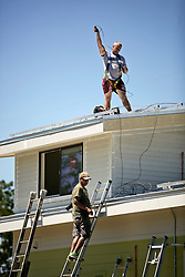 26 August 2015. New Orleans, Louisiana. <br /> Hurricane Katrina revisited. <br /> Rebuilding the Lower 9th Ward. <br /> Contractors prepare to install solar panels on a new 'Make it Right' house. Eco friendly 'Make it Right' houses inspired by actor Brad Pitt continue to provide hope for the rebirth of the community following the devastation of hurricane Katrina a decade earlier.<br /> Photo credit©; Charlie Varley/varleypix.com.