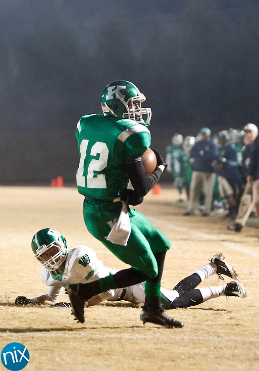 Kannapolis's Damien Washing evades a tackle by Weddington's Billy Ryan  and stays on his feet on his way to the end zone during the second round of the NCHSAA 3AA playoffs Friday night at Kannapolis Memorial Stadium. The Wonders defeated Weddington 41-20 to advance to the quarterfinals where they will meet Charlotte Catholic. (Photo by James Nix)