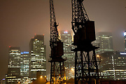 The towers of Canary Wharf on the Isle of Dogs in early winter morning darkness. The cranes are from a time when the Docklands were used as a port of entry to London. Now, a major part of London's financial district is based in the Canary Wharf on the peninsula. West India Docks.