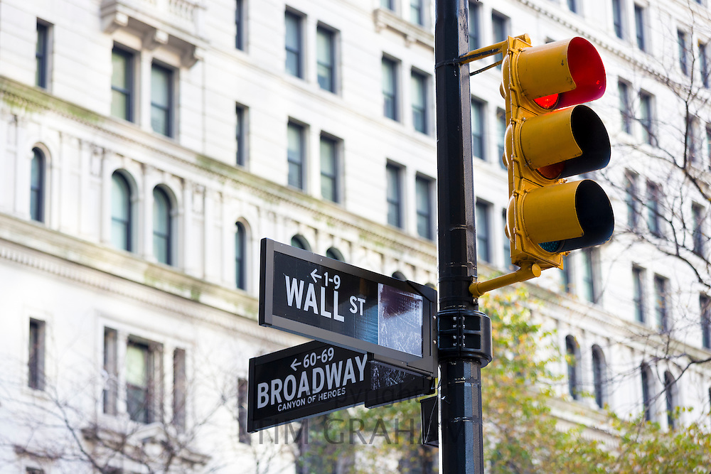 Red traffic light for STOP at corner of Wall Street and Broadway in New York, USA