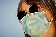 Woman wearing a protective medical face mask during coronavirus lockdown