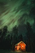 Alaska. Talkeetna. Winter cabin with Northern Lights (Aurora borealis) above. PR
