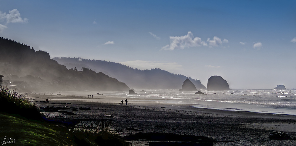 An early morning view of the beach, in Cannon Beach, Oregon, with lifting mists and beachcomers.