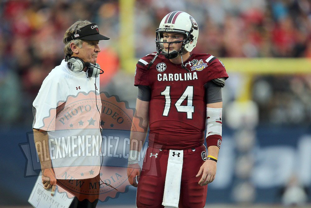 South Carolina head coach Steve Spurrier speaks to South Carolina Gamecocks quarterback Connor Shaw (14) during the NCAA Capital One Bowl football game between the South Carolina Gamecocks who represent the SEC and the Wisconsin Badgers who represent the Big 10 Conference, at the Florida Citrus Bowl on Wednesday, January 1, 2014 in Orlando, Florida. (AP Photo/Alex Menendez)