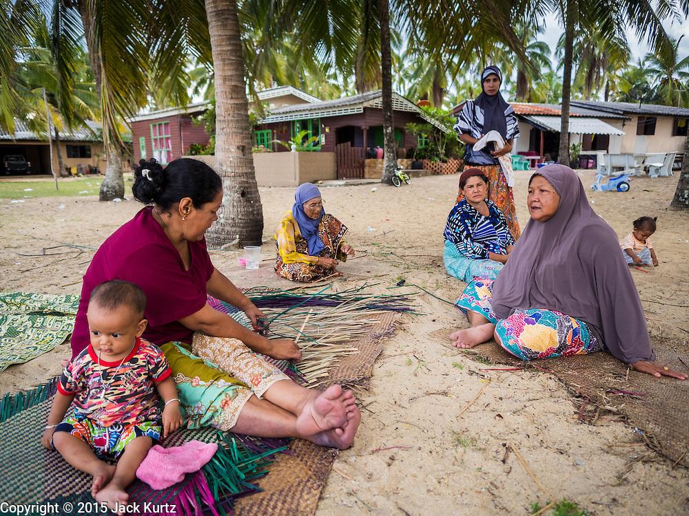 15 JUNE 2105 - BAN THONG, NARATHIWAT, THAILAND: Wives of fisherman socialize under palm trees on Ban Thong beach in Narathiwat.       PHOTO BY JACK KURTZ