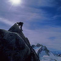 13-year old Ben Wiltsie climbs the Cain Route on Bugaboo Spire in Bugaboo Provincial Park, British Columbia, Canada.  Behind him are the Vowell Glacier and the Howser Spire Massif.