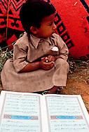 Jaber Al Amrah in front of his cousin's Qur'an at  Al Murrah encampment in the Dahana Sands, Saudi Arabia