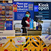 Coronavirus threat - A Tesco Express lady wearing mask and a barrage between and the customer no touching, keep distance policy on 23 March in Leyton,Tesco,Tesco Express, London, UK.