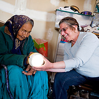 032713     Brian Leddy<br /> Marsha Monestersky shows a rechargable solar light to Alice Dougi at her home near Bodaway Gap Wednesday, March 27. Eagle Energy, a non-profit that helps install low cost solar installations, visited her home.