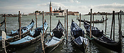 Toned photo of a row of gondolas parked in the Venice lagoon with Guidecca Island in the distance