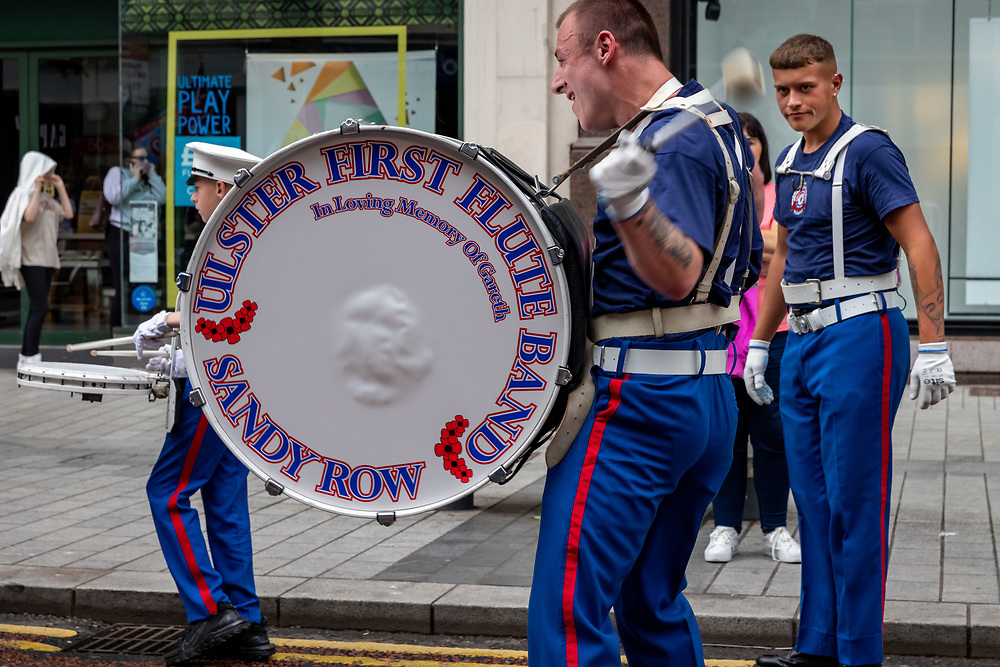 Drummer beats the bass drum with vigour and passion. Ulster First Elite Band, Sandy Row.