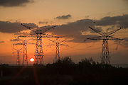 Israel, Hadera, Silhouette of high voltage power lines and the at sunset