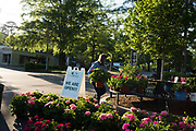 """BIRMINGHAM, AL – MAY 7, 2020: Pam Watson sets out plants at the Leaf & Petal garden store in Mountain Brook Village. Watson, who manages the store, says business has boomed throughout the pandemic. """"When people are staying home, they want to nest. So it's been nonstop. Originally we didn't have the staff to manage the surge in business because a lot of our employees decided to self quarantine. But we've managed."""" Watson said she's fortunate for the business, but ultimately the shop's wellbeing depends on jobs and the economy at large. """"Ultimately if people aren't making money, we'll feel it.""""  CREDIT: Bob Miller for The New York Times"""