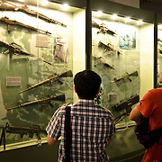 Two visitors look at a glass case of some of the weapons used by American and South Vietnamese forces during the Vietnam War at the War Remnants Museum in Ho Chi Minh City (Saigon), Vietnam.
