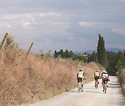 Cyclists bike down a country path in the Tuscan countryside, near medieval hilltop town San Gimignano, Italy