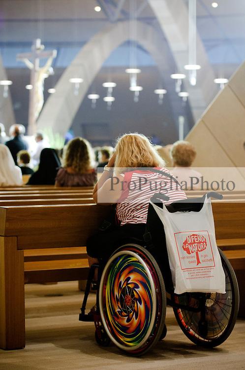 """È stata inaugurata il 1° luglio 2004, la nuova Chiesa di San Pio da Pietrelcina progettata dall'architetto Renzo Piano. Esattamente 45 anni prima, nel 1959,  veniva inaugurata la chiesa """"grande"""" di Santa Maria delle Grazie. .Sorta a fianco del santuario e convento in cui visse il frate, ha la forma di una conchiglia e la sua pianta ricorda quella della spriale archimedea. Enormi archi parto dal perimetro esterno e terminano nel fulcro della """"conchiglia"""" dove è posto l'altare. Possenti staffe d'acciaio, ancorate agli archi, sorreggono la volta che ricoperta di rame preossidato espone alla vista un intenso un colore verde-rame.   .Con i suoi 6000 mq, è la seconda chiesa più grande in Italia per dimensioni, dopo il Duomo di Milano. Può ospitare oltre 7000 persone e per la sua realizzazione sono state impiegati 30.000 metri cubi di calcestruzzo, 1.320 blocchi in pietra di Apricena, 70.000 metri cubi di scavo in roccia, 60.000 chili di acciaio, 500 mq di vetro, 19.500 mq di rame preossidato. Ogni anno è meta di oltre sei milioni di pellegrini..Nella foto la parte interna della chiesa con i suoi archi che si incrociano in un gioco di linee curve mentrw è in corso una celebrazione eucaristica. In primo piano una donna diversamente abile raccolta in preghiera."""