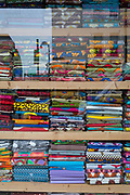 Sagging shelves, heavy with the weight of colourful, imported fabrics in an East End street, on 14th February 2018, in London, England.