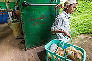 15 JUNE 2013 - YANGON, MYANMAR:  A snack vendor leans out the door of the Yangon Circular Train. The Yangon Circular Railway is the local commuter rail network that serves the Yangon metropolitan area. Operated by Myanmar Railways, the 45.9-kilometre (28.5mi) 39-station loop system connects satellite towns and suburban areas to the city. The railway has about 200 coaches, runs 20 times and sells 100,000 to 150,000 tickets daily. The loop, which takes about three hours to complete, is a popular for tourists to see a cross section of life in Yangon. The trains from 3:45 am to 10:15 pm daily. The cost of a ticket for a distance of 15 miles is ten kyats (~nine US cents), and that for over 15 miles is twenty kyats (~18 US cents). Foreigners pay 1 USD (Kyat not accepted), regardless of the length of the journey.     PHOTO BY JACK KURTZ