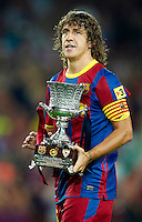 BARCELONA, SPAIN - AUGUST 21: Carles Puyol of FC Barcelona holds the trophy after the Supercopa, second leg, match between Barcelona and Sevilla at the Camp Nou stadium on August 21, 2010 in Barcelona, Spain. Barcelona 4-0. (Photo by Manuel Queimadelos Alonso/Getty Images) *** Local Caption *** Carles Puyol