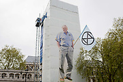 An image of veteran wildlife and environmental broadcaster Sir David Attenborough is held high in Parliament Square during the week-long protest by climate change activists with Extinction Rebellions campaign to block road junctions and bridges around the capital, on 23rd April 2019, in London England.