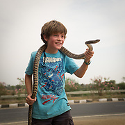 Boy holds a snake excitedly.