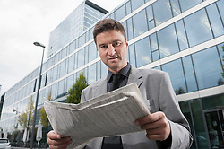 Businessman reading a newspaper outside office building, Bavaria, Germany