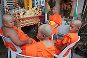 "Mar. 21, 2009 -- BANGKOK, THAILAND: Buddhist monks relax in the Monk's Bowl Village in Bangkok. The Monk's Bowl Village on Soi Ban Baat in Bangkok is the only surviving one of what were originally three artisan's communities established by Thai King Rama I for the purpose of handcrafting ""baat"" the ceremonial bowls used by monks as they collect their morning alms. Most monks now use cheaper factory made bowls and the old tradition is dying out. Only six or seven families on Soi Ban Baat still make the bowls by hand. Most of the bowls are now sold to tourists who find their way to hidden alleys in old Bangkok. The small family workshops are only a part of the ""Monk's Bowl Village."" It is also a thriving residential community of narrow alleyways and sidewalks.     Photo by Jack Kurtz"